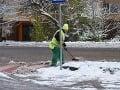 Pracovník Správy mestských komunikácií odpratáva sneh z chodníkov.