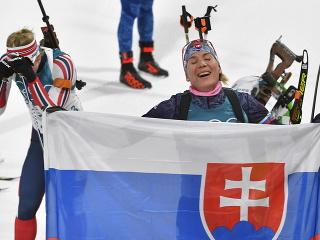 Na snímke slovenská biatlonistka Anastasia Kuzminová drží slovenskú vlajku v cieli po zisku zlatej olympijskej medaily
