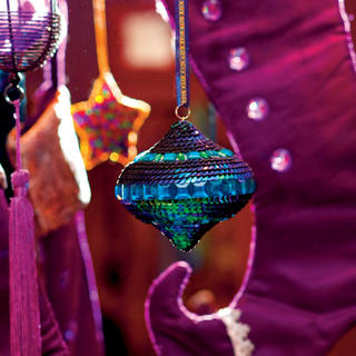 Vianočná ozdoba ztrblietavých tyrkysových amodrých flitrov, cena 128 Sk; fialová čižma zdobená bielymi brúsenými kameňmi ačipkou, cena 485 Sk; ružový lampášik vpuzdre zčierneho drôtu, cena 268 Sk; jagavá hviezda vyšívaná farebnými perličkami, cena 85