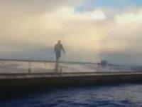 Rybár kráčajúci po móle vyzerá ako duch.