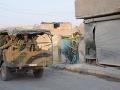 Tureckí vojaci na aute prechádzajú okolo domu, ktorý bol zasiahnutý počas mínometného útoku v tureckom meste Akcakale.
