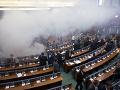 Kosovskí poslanci odchádzajú po tom, čo opoziční poslanci hodili kanistre so slzotvorným plynom počas zasadnutia parlamentu 21. marca 2018 v Prištine.