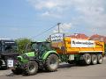 Kolóna strojov s transparentmi počas protestnej jazdy farmárov na traktoroch.