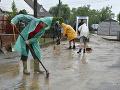 Na snímke odpratávanie vody a bahna zo zaplavenej ulice v obci Ratnovce.
