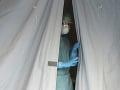 Zdravotníčka sa pozerá z jedného zo stanov pred nemocnicou v talianskom meste Brescia