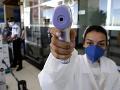 Brazílska zdravotníčka kontroluje teplotu