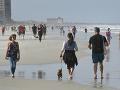 Ľudia kráčajú na pláži