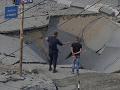 Ľudia stoja na zničenej ulici po útoku v pásme Gazy