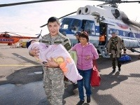 Záchranár nesie chlapčeka na rukách