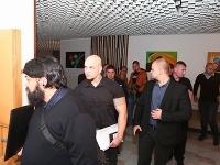 Obvinení muži vchádzajú do pojednávacej miestnosti