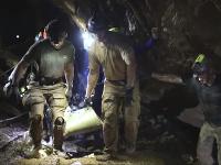 Fotografia ukazuje záchranárov, ako vyvádzajú jedného z chlapcov vnútri jaskyne.