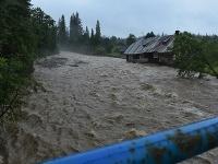 Rozvodnený potok Javorinka, ktorý berie so sebou starší dom v Podspádoch vo Vysokých Tatrách.