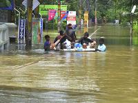 Ľudia sa pohybujú po zaplavenej oblasti v Thrissure, v juhoindickom štáte Kérala