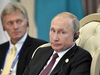 Vladimír Putin, v pozadí Dmitrij Peskov