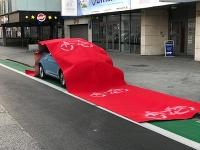 Červený koberec na vozidle, ktoré bolo zaparkované na cyklochodníku.
