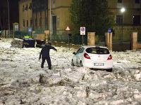 Muž sa snaží dostať k autu po zľadovatenej ceste po krupobití v Ríme