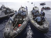 Potápači vylovujú z vody rôzne predmety z havarovaného lietadla.