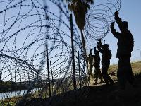 Americký vojaci na hranici naťahujú ostnatý drôt.
