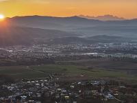 Na snímke v popredí obec Ruská Nová Ves, uprostred Prešov a vpravo hore Vysoké Tatry v posledných lúčoch slnka.