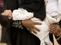 Na archívnej snímke z 18. apríla 2017 žena drží novorodené dieťa v jednej ruke počas úteku z Mósulu.