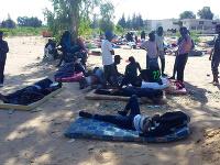 Migranti oddychujú pred detekčným centrom po leteckom nálete na predmestí Tripolisu.