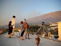 Miestni obyvatelia sledujú požiar zo strechy domu na aténskom predmestí Peania