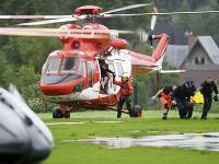 Záchranári prenášajú z helikoptéry do sanitky prvých ľudí zranených počas búrky s bleskami 22. augusta 2019 v poľskom Zakopanom.