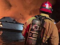 Hasič zasahuje počas požiara, ktorý vypukol na lodi s desiatkami pasažierov