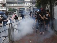 Ľudia si zakrývajú tvár pri zásahu polície slzotvorným plynom na demonštrantov počas protestu v Hongkongu