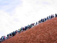 Turisti v húfoch lezú na posvätnú horu