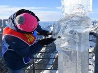 Na snímke účastník medzinárodných majstrovstiev v stavaní ľadových sôch Tatry Ice Master z Mongolska vyrezáva detaily sochy symbolizujúcej klimatické zmeny na Lomnickom štíte vo Vysokých Tatrách
