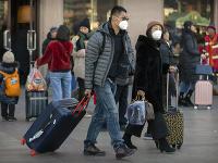 Cestujúci majú na tvári ochranné rúška pred železničnou stanicou v Pekingu