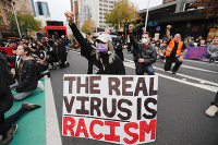 Demonštranti držia transparent počas protestného pochodu v centrálnom Aucklande na Novom Zélande