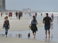 Ľudia kráčajú na pláži počas pandémie nového koronavírusu v Jacksonville Beach na Floride.