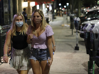 Ženy s ochrannými rúškami na zabránenie šírenia nového koronavírusu kráčajú po ulici v centre Atén.