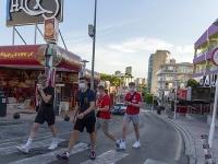 Turisti s ochrannými rúškami kráčajú po ulici v letovisku Magaluf