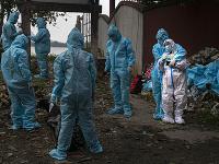 Žena v bielom ochrannom oblečení reaguje po tom, čo videla telo svojho manžela, obete koronavírusu v indickom meste Gauháti.