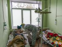 Lekár v špeciálnom ochrannom odeve  sa rozpráva s pacientom infikovaným novým typom koronavírusu na Ukrajine