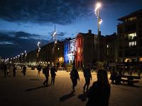 Ľudia kráčajú okolo radnice, ktorá je vysvietená vo farbách francúzskej vlajky na pamiatku zosnulého učiteľa dejepisu