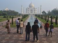 Malá skupina indických turistov stojí pred pamätníkom Tádž Mahal v meste Ágra.