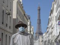 Muž chrániaci sa rúškom pred Eiffelovou vežou v Paríži