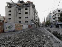 Ľudia sledujú trosky zničenej kliniky zdravotnej starostlivosti v blízkosti ministerstva zdravotníctva v Gaze po izraelskom nálete na horné poschodia budovy.