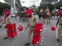 Indickí policajti kráčajú v prilbách v tvare nového typu koronavírusu počas akcie zameranej na prevenciu jeho šírenia.