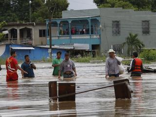 Muži sa brodia po zaplavenej cesta po vyčíňaní hurikánu Iota v honduraskom meste La Lima