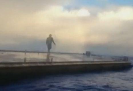 Rybár kráčajúci po móle