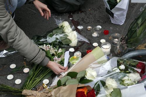 Ľudia zapaľujú sviečky obetiam