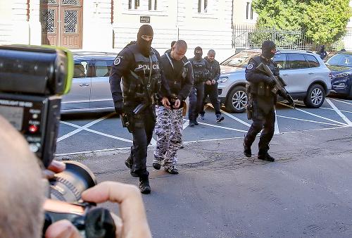 Na snímke polícia privádza
