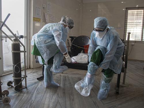 Zdravotníci v ochranných oblekoch