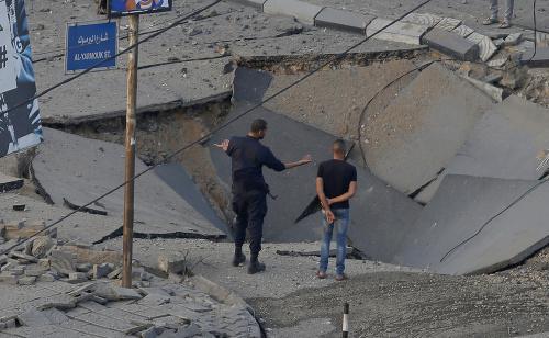 Ľudia stoja na zničenej