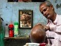 Pouličný holič holí zákazníka